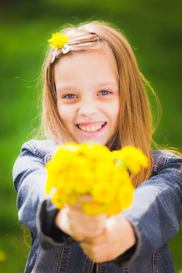 Portrait of smiling young girl holding bouquet of flowers in han stock image