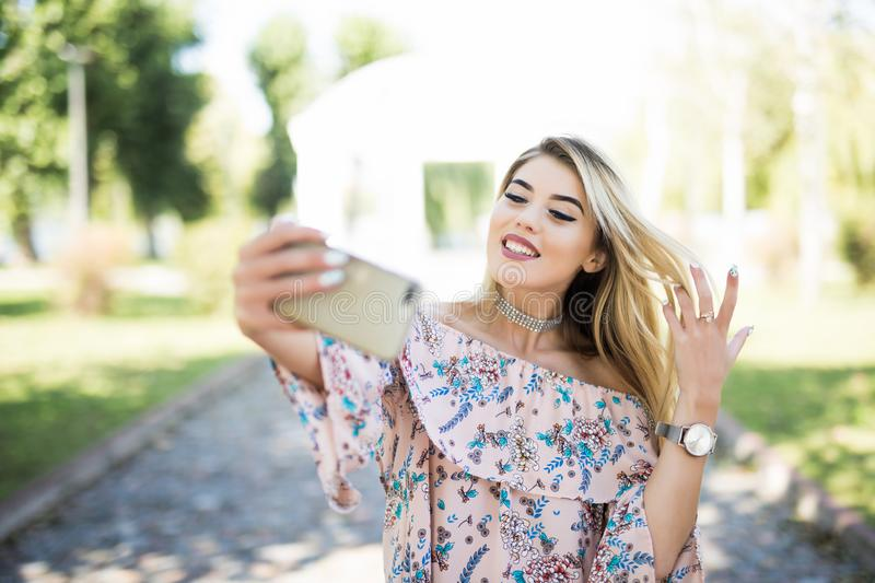 POrtrait of a smiling young girl making selfie photo phone in park stock photo