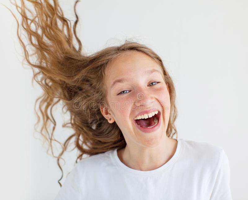 Portrait smiling young girl teen with flying curly hair royalty free stock photo