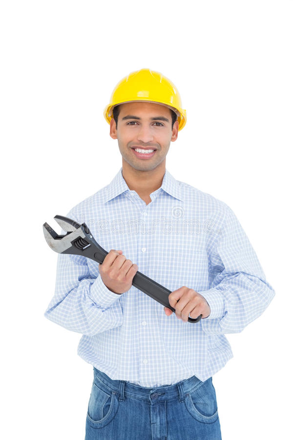 Portrait of a smiling young handyman holding a wrench stock photo