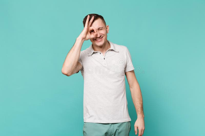 Portrait of smiling young man in casual clothes standing, showing OK gesture near eyes isolated on blue turquoise. Background in studio. People sincere emotions royalty free stock images