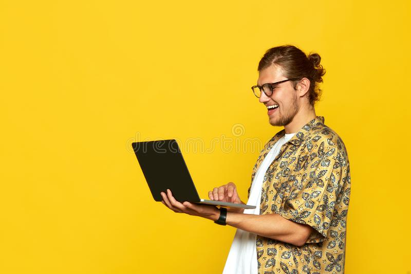 Portrait of a smiling young man in eyeglasses using laptop computer over orange background royalty free stock image