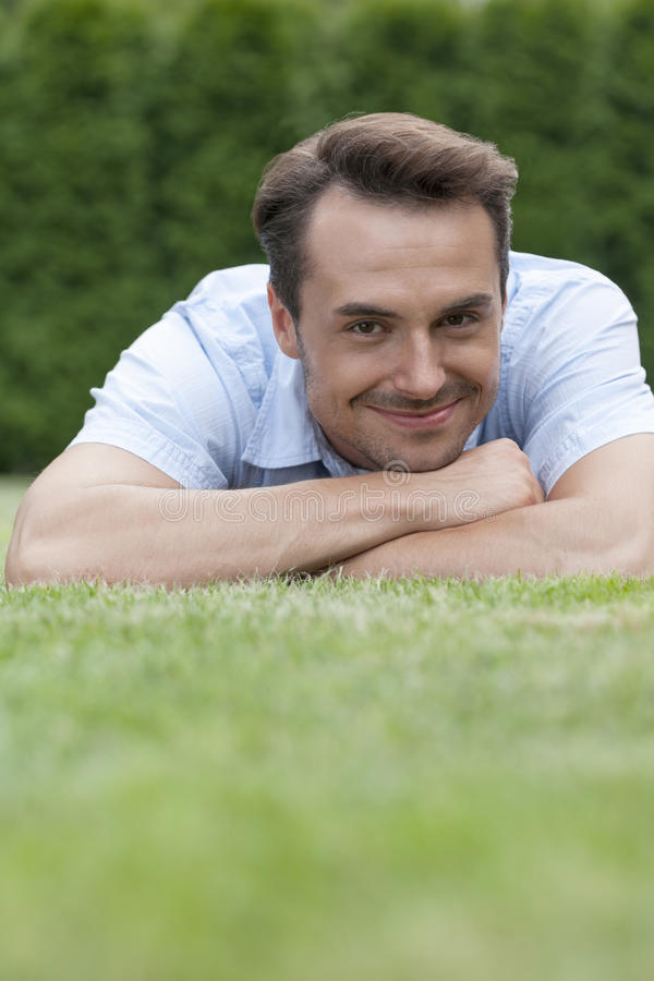 Portrait of smiling young man lying on grass in park stock photo