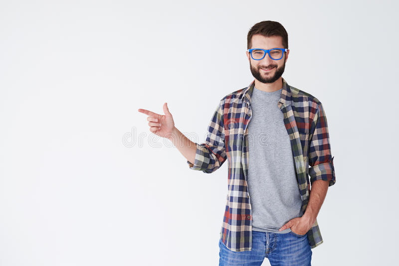 Portrait of a smiling young man pointing sideway royalty free stock image