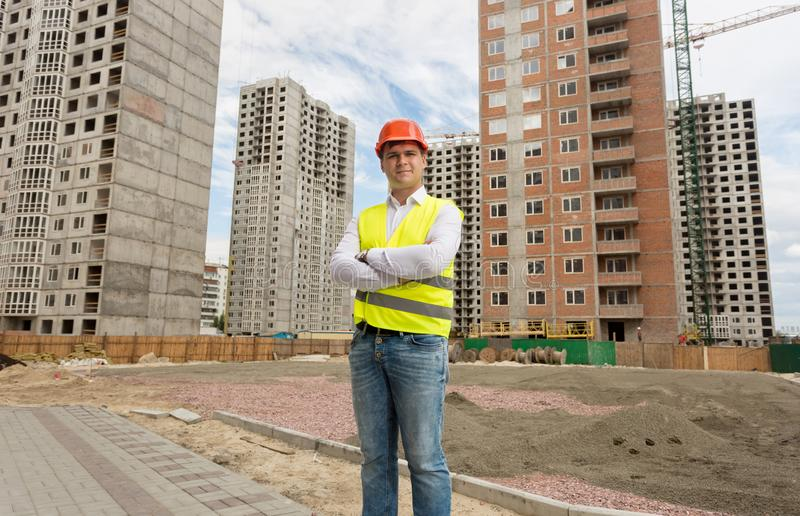 Portrait of smiling young man in safety vest and helmet posing over buildings under ocnstruction royalty free stock images