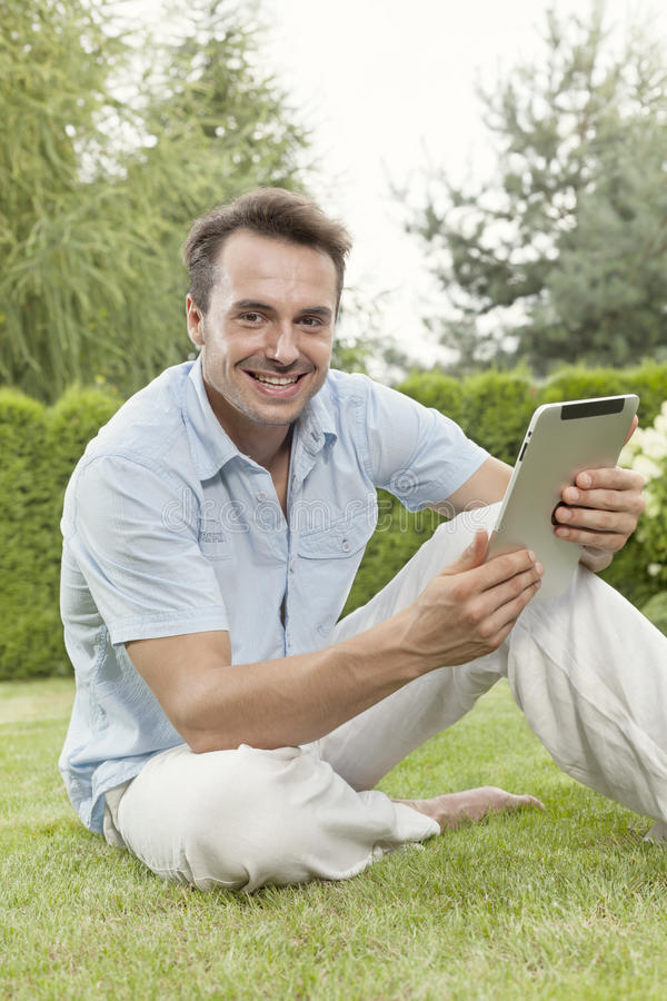 Portrait of smiling young man using tablet computer in park stock photo