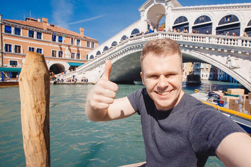 Portrait smiling young man in Venice, Italy taking selfie against backdrop great canal and bridge. Concept travel stock photos