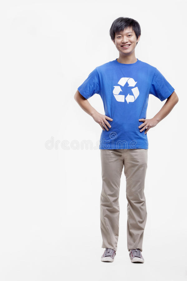 Portrait of smiling young man wearing recycling symbol T-shirt with hands on his hips, studio shot stock image
