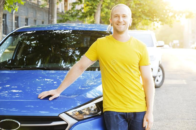 Successfull happy young man and his car in soft sunset light on urbanistic background. Busines man with vehicle on roadside. royalty free stock photography