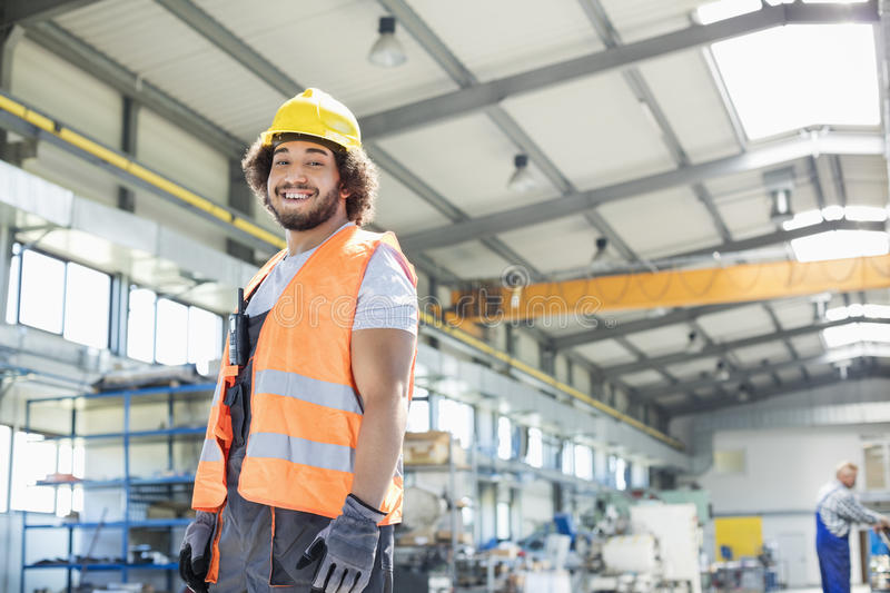 Portrait of smiling young manual worker standing in factory.  stock photo