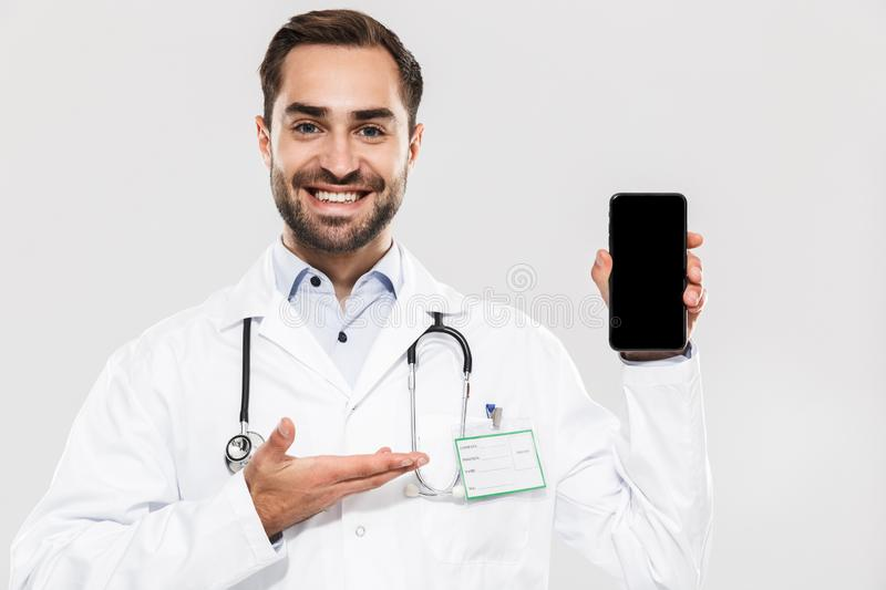 Portrait of smiling young medical doctor with stethoscope working in clinic and holding cellphone stock photos