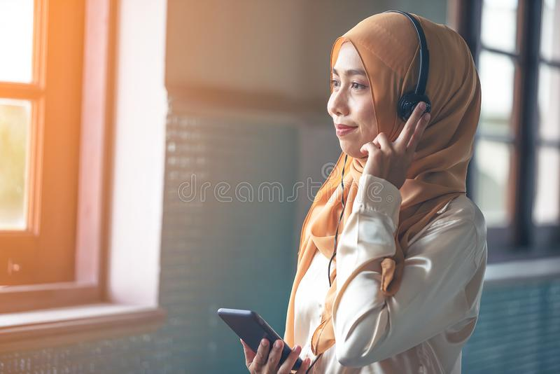 Portrait of a smiling young modern arabian woman holding mobile phone and listening the music to headphone stock image