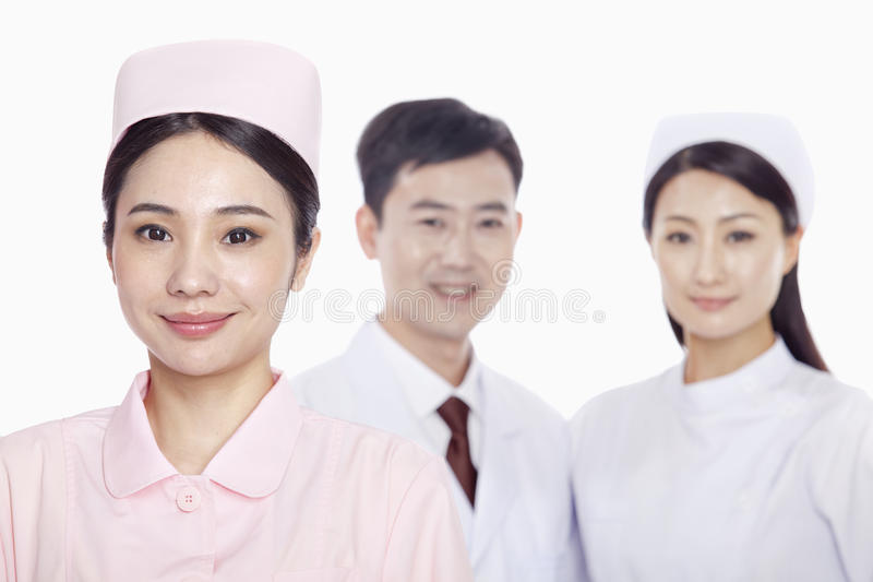Portrait of smiling young nurse, doctor and nurse in the background, studio shot royalty free stock photography