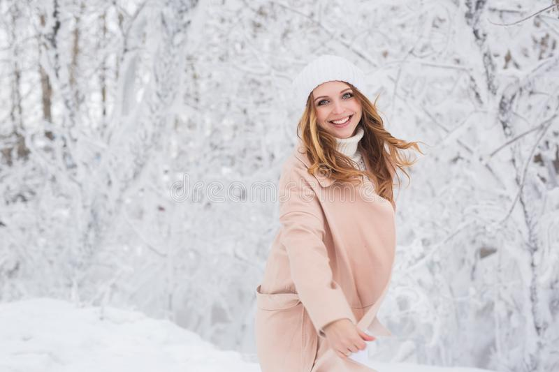 Portrait of smiling young pretty woman in a beige jacket in a winter forest stock photos