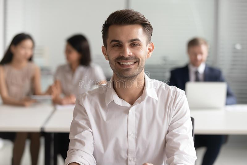 Portrait of smiling young team leader sitting at office. stock photography