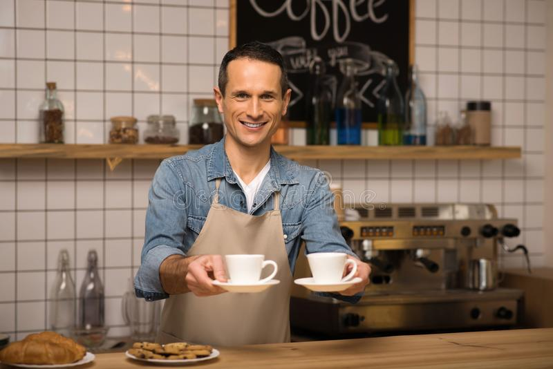 Waiter holding two cups of coffee. Portrait of smiling young waiter holding two cups of coffee and looking at camera royalty free stock photo