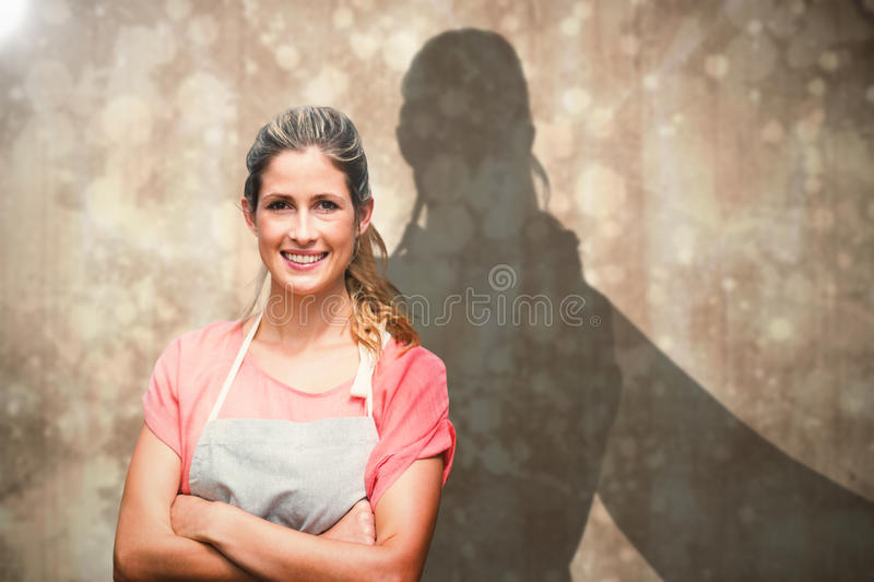 Composite image of portrait of smiling young woman with arms crossed. Portrait of smiling young woman with arms crossed against paint splattered paper stock image