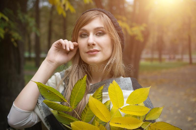 Portrait of smiling young woman with autumn leafs stock photo