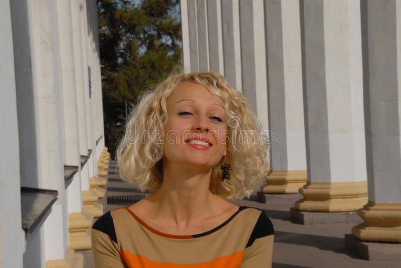 A portrait of a smiling and cheerful young woman with a blond curly hair, standing in the park. royalty free stock photo