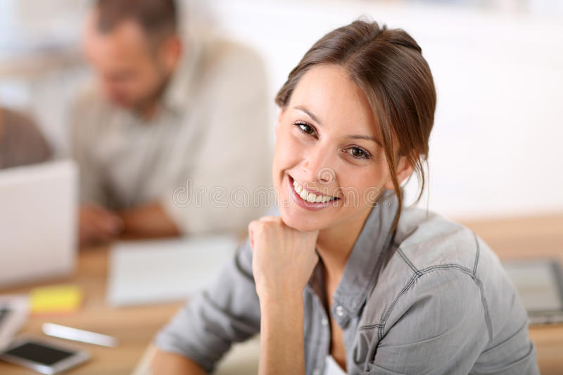 Portrait of smiling young woman in business training stock image