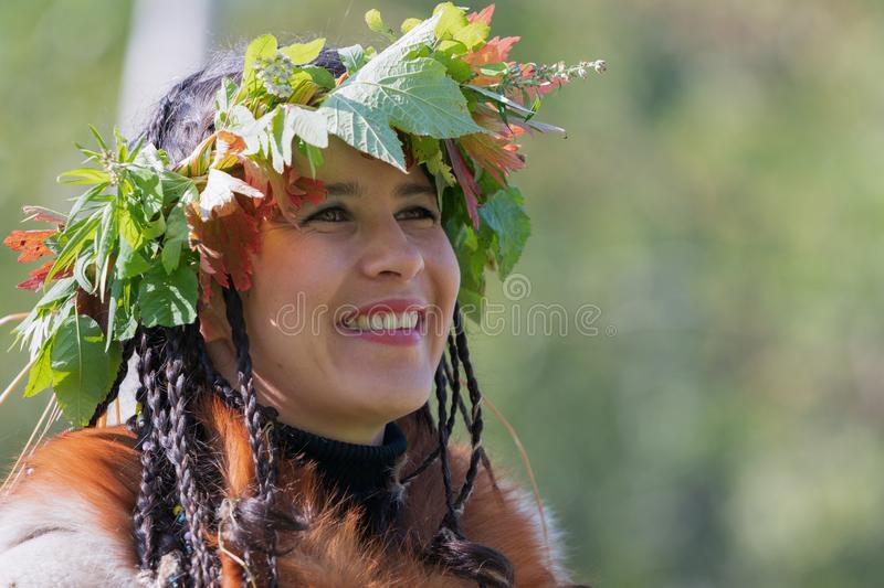 Portrait of smiling young woman in clothing aborigine of Kamchatka Peninsula stock images