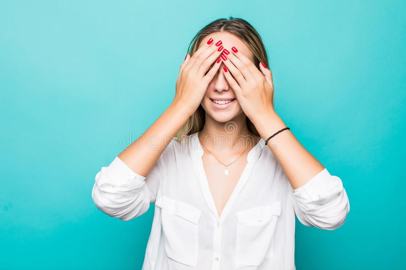 Portrait of a smiling young woman covering eyes with her arms isolated over blue background royalty free stock photo