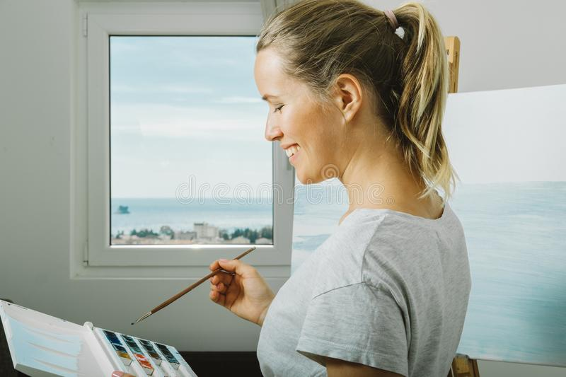 Portrait of smiling young woman drawing painting in home studio, art mental therapy. royalty free stock images