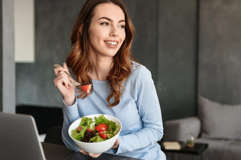 Portrait of a smiling young woman eating fresh salad. From a bowl while sitting at home royalty free stock photos