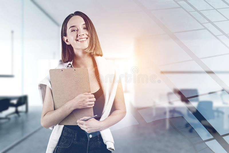 Smiling young woman with clipboard in office stock photography
