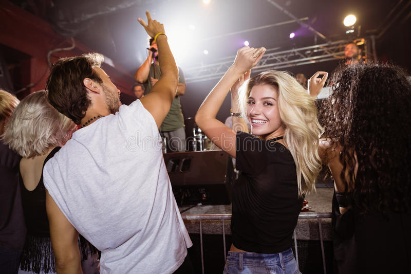 Portrait of smiling young woman with friends enjoying music concert stock photography