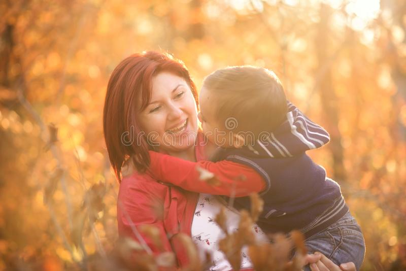 Portrait of smiling young woman holding little toddler son in arms in autumn outdoors. Happiness and family leisure concept stock photo