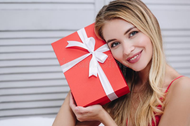 Woman holding red gift box. Portrait of smiling young woman holding red gift box at the face, valentines day concept royalty free stock images
