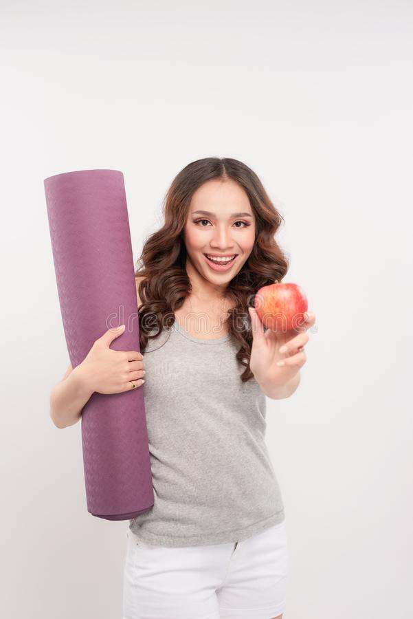 Portrait of smiling young woman holding rolled up exercise yoga royalty free stock photos