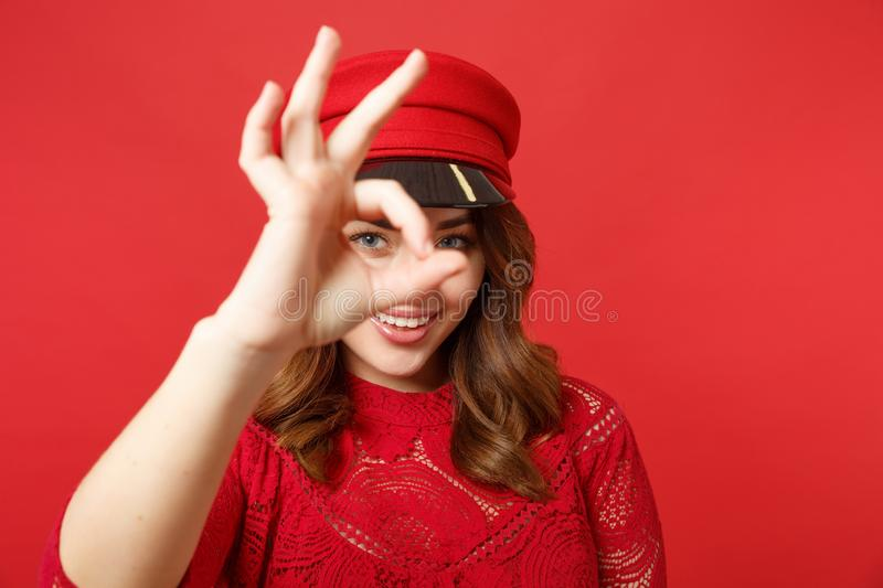 Portrait of smiling young woman in lace dress and cap showing, looking behind OK gesture isolated on bright red. Background in studio. People sincere emotions royalty free stock photos