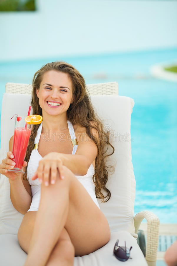 Portrait of smiling young woman laying on sunbed. And enjoying cocktail royalty free stock photography