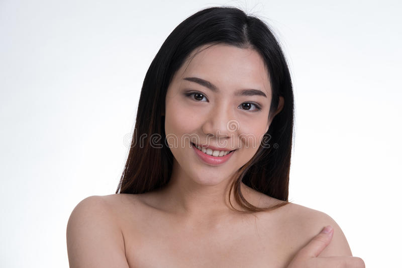 Portrait of a smiling young woman with natural make-up. beautiful asian girl standing against white background. royalty free stock photography