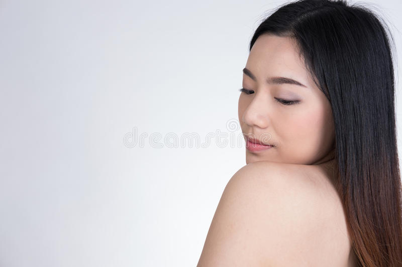 Portrait of a smiling young woman with natural make-up. beautiful asian girl standing against white background. stock photography
