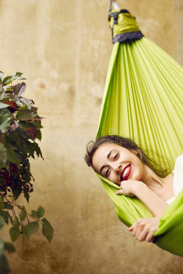 Portrait of smiling young woman relaxing in a hammock on the terrace house. stock images
