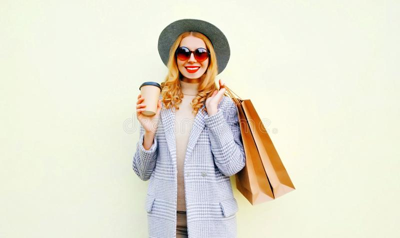 Portrait smiling young woman with shopping bags, holding coffee cup, wearing pink coat, round hat royalty free stock images