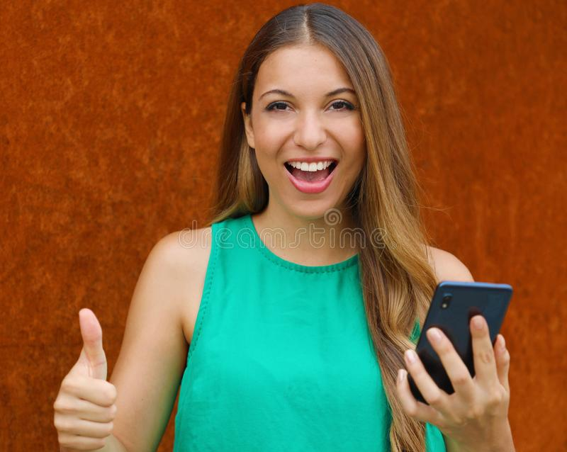 Portrait of a smiling young woman showing thumbs up gesture while holding mobile phone outdoors stock photography