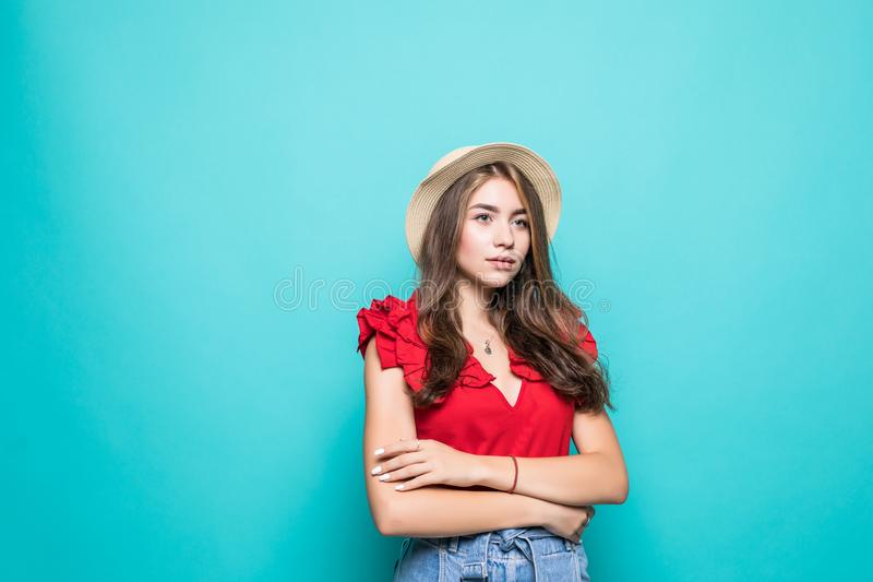 Portrait of a smiling young woman standing with arms folded and looking away at copyspace over blue background royalty free stock photos