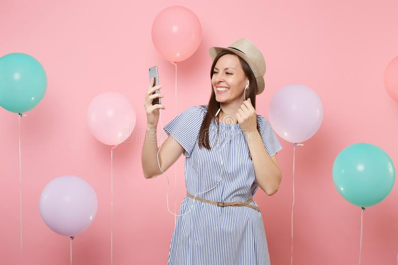 Portrait of smiling young woman in straw summer hat blue dress with mobile phone and earphones listening music making. Video call on pink background with stock image