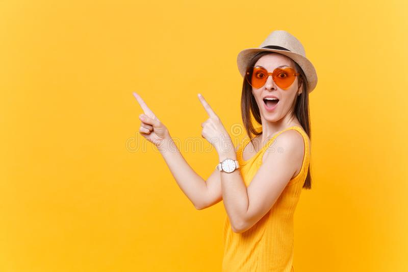 Portrait of smiling young woman in straw summer hat, orange glasses pointing index fingers aside copy space isolated on royalty free stock photos