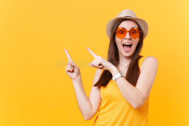 Portrait of smiling young woman in straw summer hat, orange glasses pointing index fingers aside copy space isolated on stock photo