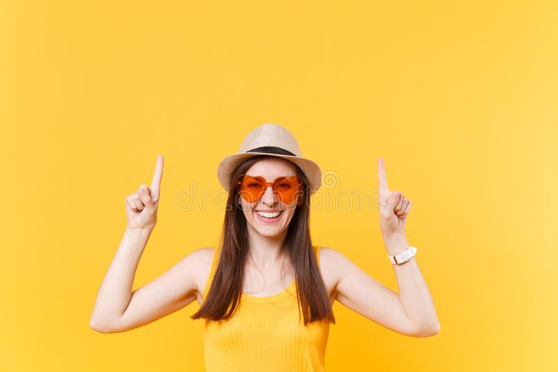 Portrait of smiling young woman in straw summer hat, orange glasses pointing index fingers up on copy space isolated on. Yellow background. People sincere royalty free stock photography