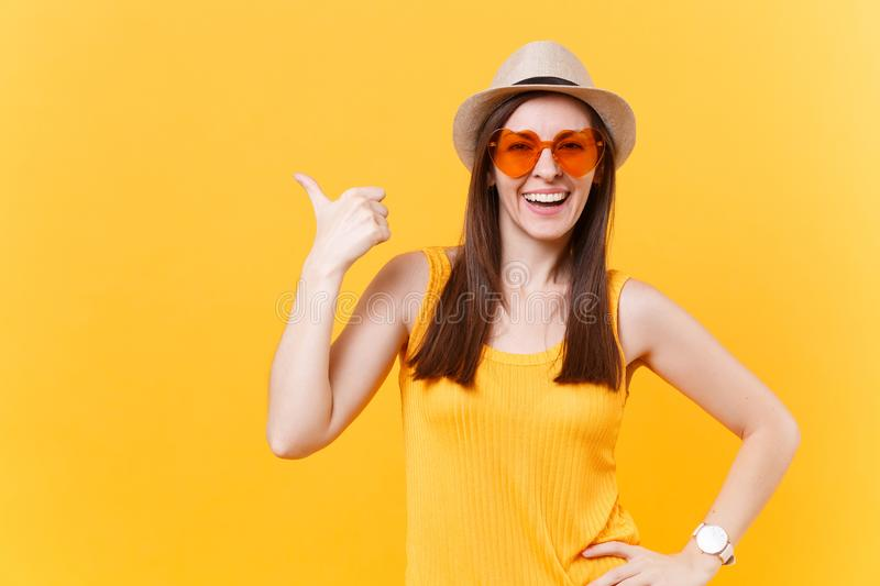 Portrait of smiling young woman in straw summer hat, orange glasses pointing right hand aside copy space isolated on stock image