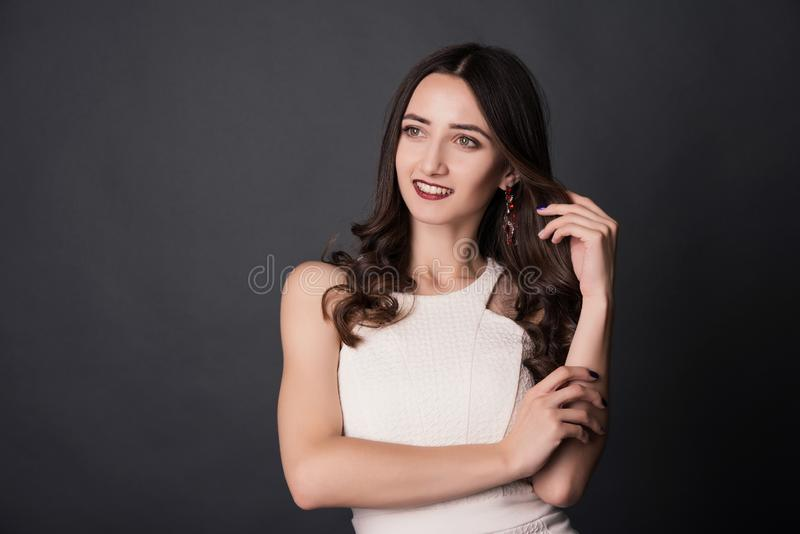 Portrait of a smiling young woman touching her hair over gray background stock photo