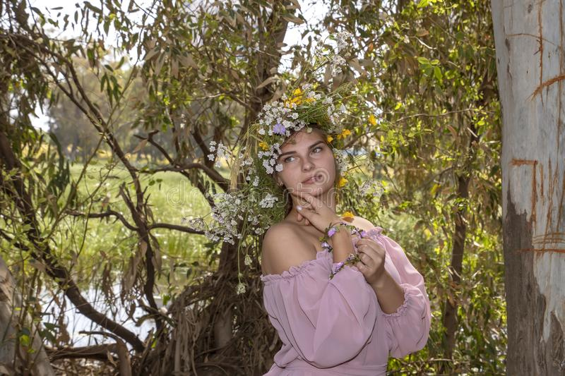 Portrait of a smiling young woman in a wreath of flowers close up leaning on a tree trunk royalty free stock photos