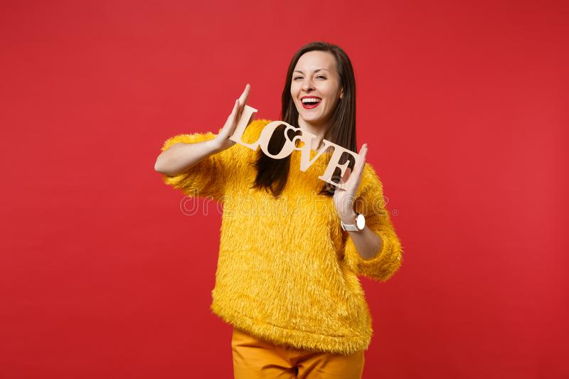 Portrait of smiling young woman in yellow fur sweater holding wooden word letters love isolated on bright red wall royalty free stock images
