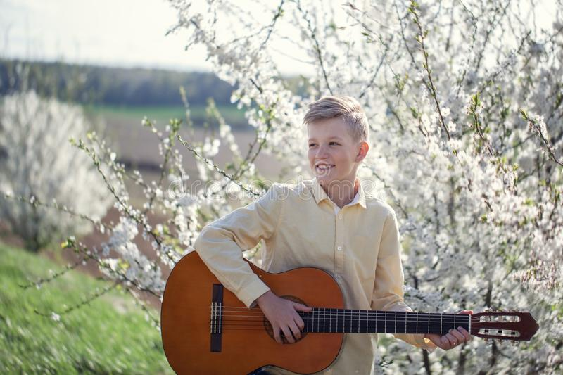 Portrait of a young 11 year old boy standing in spring park and playing guitar stock image